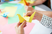 Human hands folding sheet of yellow paper while making origami bird