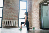 Beautiful young woman doing lunges at home.