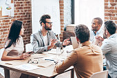 Group of young business people discussing something while sitting at the wooden table together