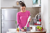 A beautiful young woman preparing a smoothie with fruits in the kitchen