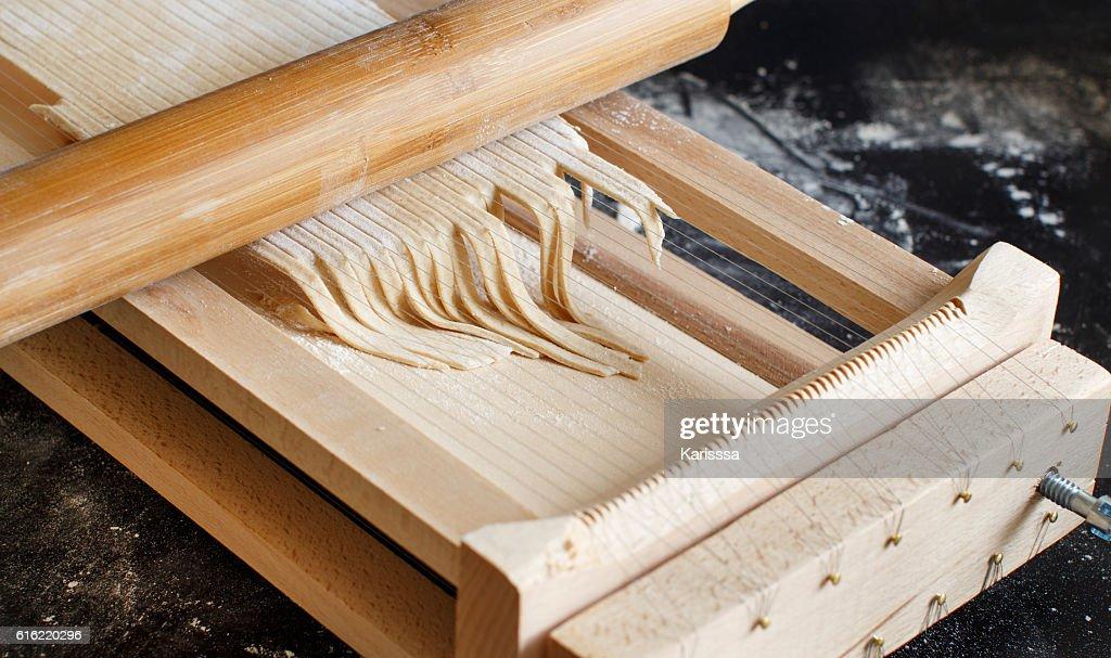 Making spaghetti alla chitarra with a tool : Stock-Foto