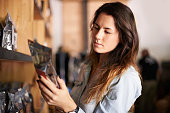 Shot of a beautiful woman in a store looking carefully at a packet of coffee beans