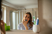 Portrait of a beautiful young woman brushing teeth in the bathroom.