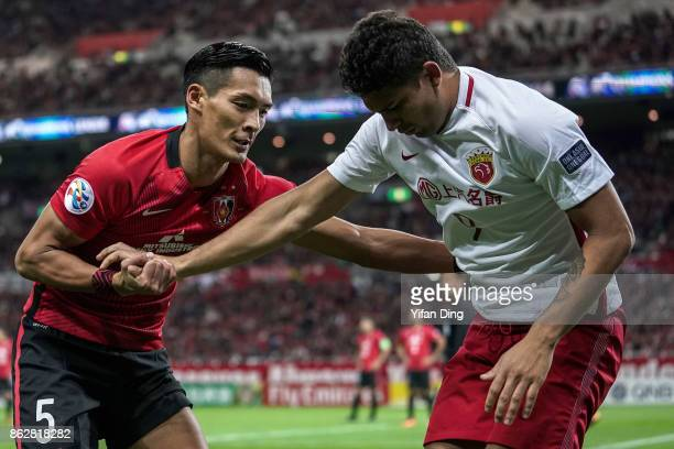 Makino Tomoaki of Urawa Red Diamonds comforts Elkeson of Shanghai SIPG during the AFC Champions League semi final second leg match between Urawa Red...