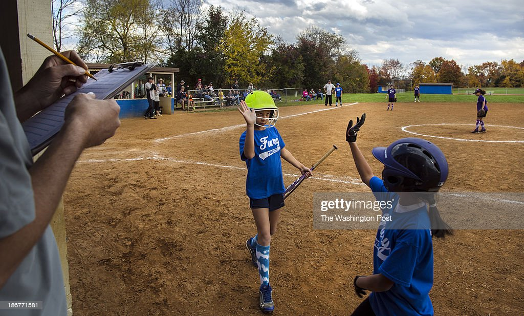 Makiya Hines (left) high fives Fury teammate Vivian Peregrino, November, 2, 2013, at Tyler Elementary school in Gainesville, VA, during a Prince William County Girls Softball Little League game. In the New Virginia, in parts of Prince William County, people come from Fairfax and Arlington and India and El Salvador, to find yards for their kids and houses they can afford. Two men are running for governor but there is little talk about what it's like to spend four hours a day commuting so that your kids can go to good schools, or about what roads could be built so it might not take an hour out of your Saturday to go to the dry cleaner.