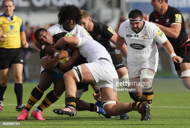 Mako Vunipola of Saracens is tackled by Ashley Johnson and Marcus Garratt during the Aviva Premiership match between Saracens and Wasps at Allianz...