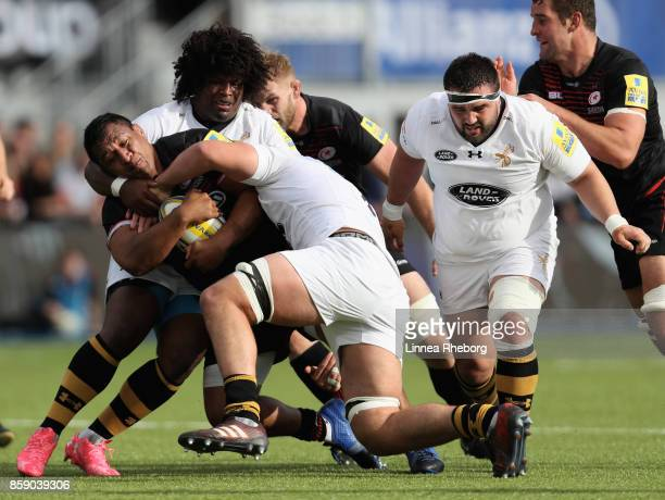 Mako Vunipola of Saracens is tackled by Ashley Johnson and Marcus Garrett during the Aviva Premiership match between Saracens and Wasps at Allianz...