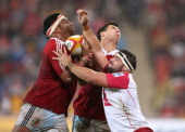 Mako Vunipola of the Lions and Ben Youngs are tackled by James Hanson during the match between the Queensland Reds and the British Irish Lions at...