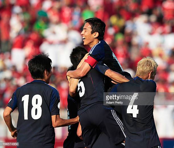 Makoto Hasebe congratulates Hiroshi Kiyotake of Japan after scoring the first goal during the FIFA World Cup Asian qualifier match between Oman and...