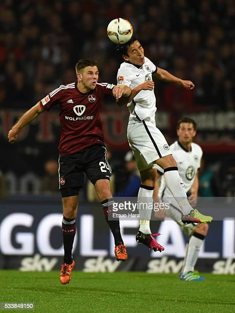 Makoto Hasebe of Eintracht Frankfurt and Niclas Fuellkrug of 1FC Nuernberg compete for the ball during the Bundesliga Playoff second leg match...