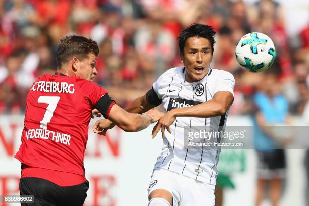 Makoto Hasebe of Frankfurt battles for the ball with Florian Niederlechner during the Bundesliga match between SportClub Freiburg and Eintracht...