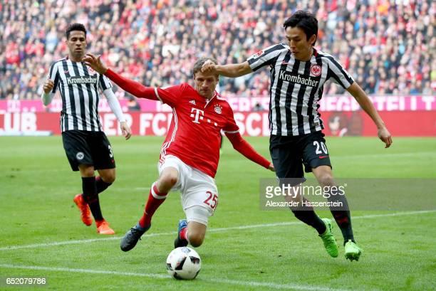 Makoto Hasebe of Frankfurt challenges Thomas Mueller of Muenchen during the Bundesliga match between Bayern Muenchen and Eintracht Frankfurt at...