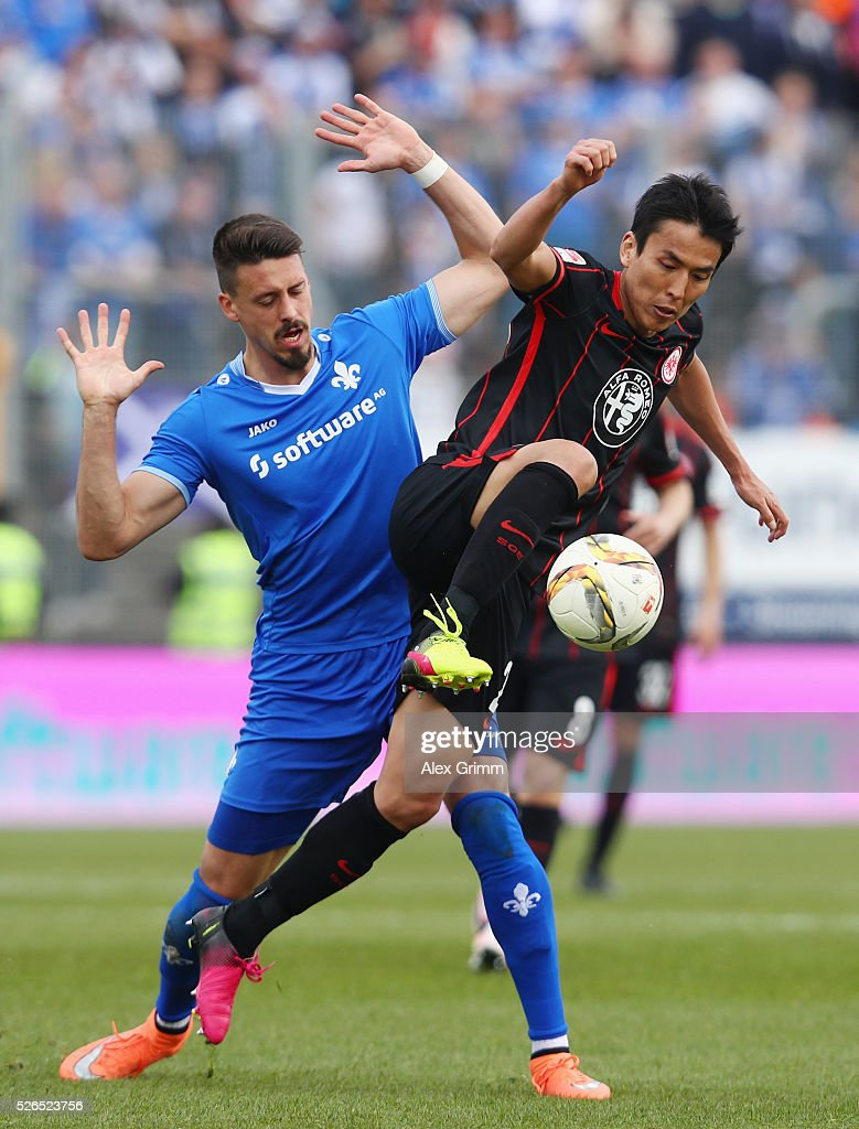 Makoto Hasebe (front) of Frankfurt is challenged by Sandro Wagner of Darmstadt during the Bundesliga match between SV Darmstadt 98 and Eintracht Frankfurt at Merck-Stadion am Boellenfalltor on April 30, 2016 in Darmstadt, Hesse.