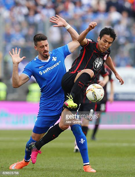 Makoto Hasebe of Frankfurt is challenged by Sandro Wagner of Darmstadt during the Bundesliga match between SV Darmstadt 98 and Eintracht Frankfurt at...