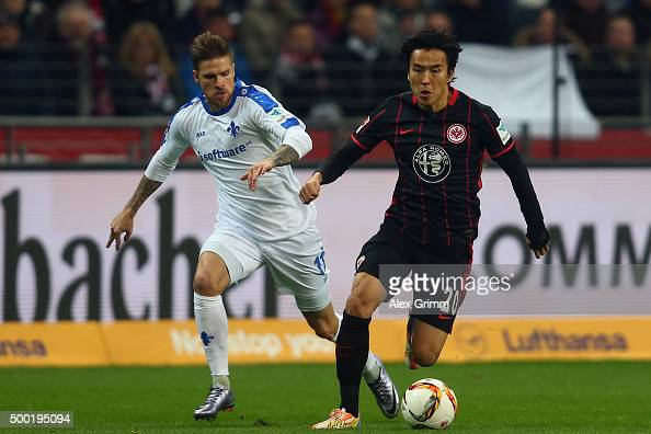 Makoto Hasebe of Frankfurt is challenged by Tobias Kempe of Darmstadt during the Bundesliga match between Eintracht Frankfurt and SV Darmstadt 98 at...