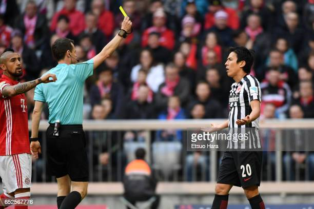 Makoto Hasebe of Frankfurt is shown an yellow card during the Bundesliga match between Bayern Muenchen and Eintracht Frankfurt at Allianz Arena on...