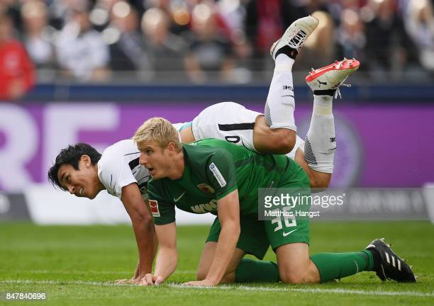 Makoto Hasebe of Frankfurt is tackled by Martin Hinteregger of Augsburg during the Bundesliga match between Eintracht Frankfurt and FC Augsburg at...