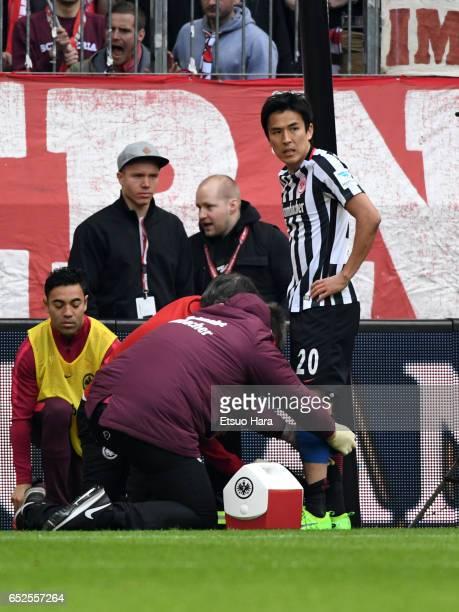 Makoto Hasebe of Frankfurt receives medical treatment during the Bundesliga match between Bayern Muenchen and Eintracht Frankfurt at Allianz Arena on...