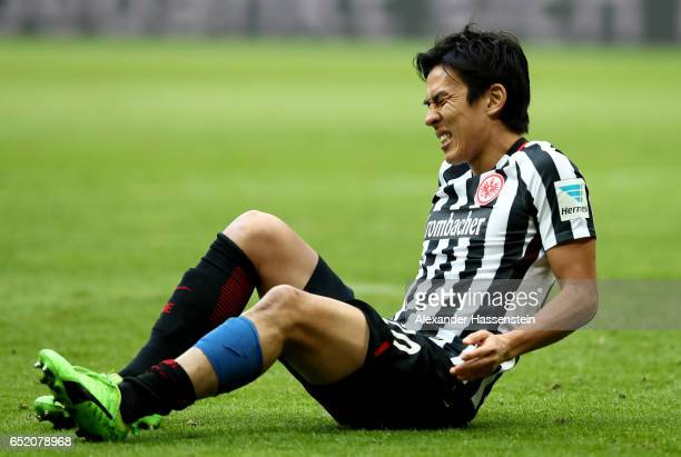 Makoto Hasebe of Frankfurt sits injurd on the pitch during the Bundesliga match between Bayern Muenchen and Eintracht Frankfurt at Allianz Arena on...