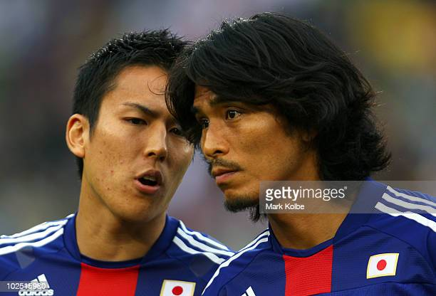 Makoto Hasebe of Japan speaks to team mate Yuji Nakazawa ahead of the 2010 FIFA World Cup South Africa Round of Sixteen match between Paraguay and...