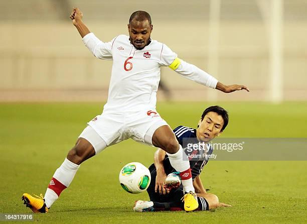 Makoto Hasebe of Japan tackles Julian De Guzman of Canada during the international friendly match between Japan and Canada at Khalifa International...