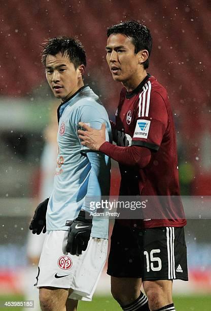 Makoto Hasebe of Nuernberg holds back Shinji Okazaki of Mainz after Okazaki had strong words with the referee during the Bundesliga match between FC...