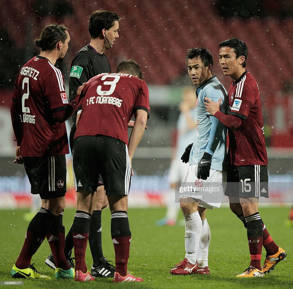 Makoto Hasebe of Nuernberg holds back Shinji Okazaki of Mainz after Okazaki had strong words with the referee during the Bundesliga match between FC...