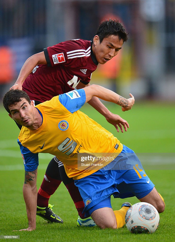 <a gi-track='captionPersonalityLinkClicked' href=/galleries/search?phrase=Makoto+Hasebe&family=editorial&specificpeople=876998 ng-click='$event.stopPropagation()'>Makoto Hasebe</a> of Nuernberg is challenged by Norman Theuerkauf of Braunschweig during the Bundesliga match between Eintracht Braunschweig and 1. FC Nuernberg at Eintracht Stadion on September 15, 2013 in Braunschweig, Germany.