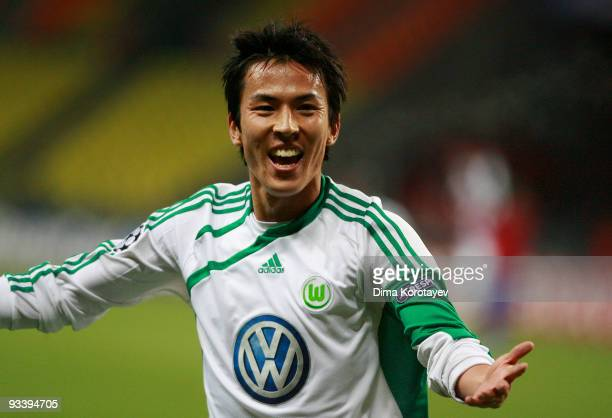 Makoto Hasebe of VfL Wolfsburg celebrates after his team mate Edin Dzeko scored the first goal during the UEFA Champions League group B match between...