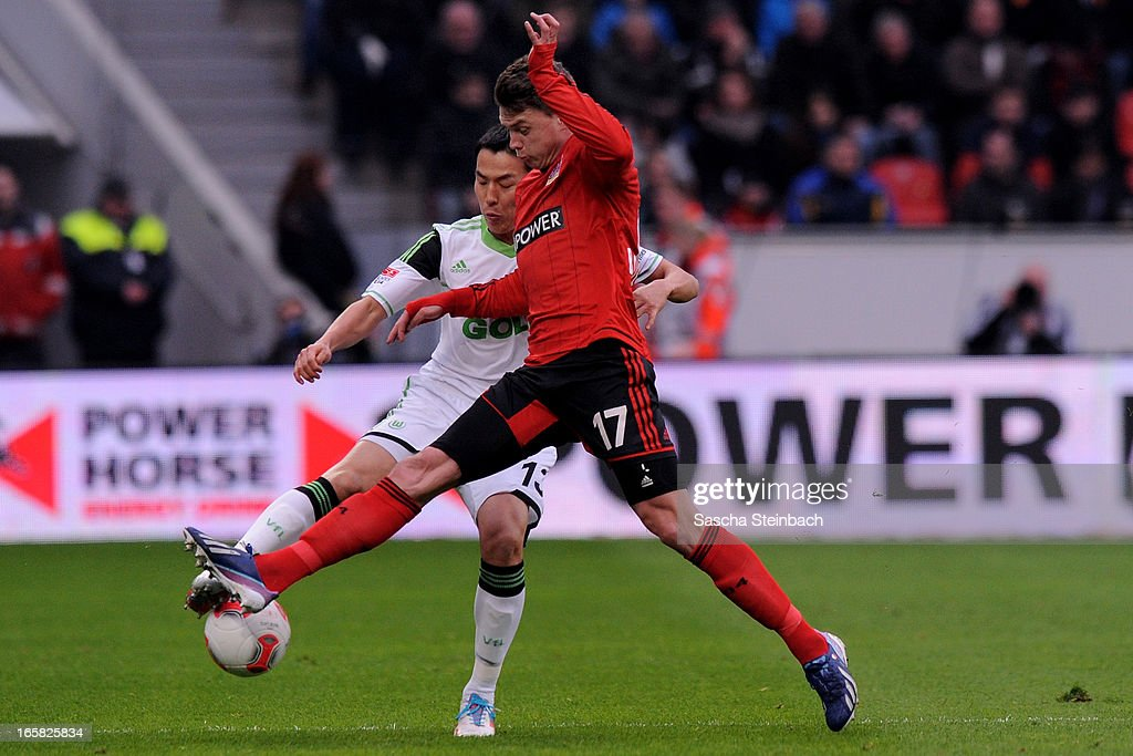 Makoto Hasebe of Wolfsburg (L) and Sebastian Boenisch of Leverkusen (R) battle for the ball during the Bundesliga match between Bayer 04 Leverkusen and VfL Wolfsburg at BayArena on April 6, 2013 in Leverkusen, Germany.