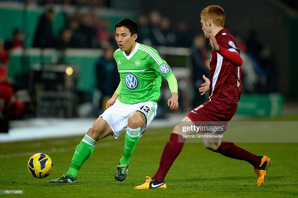 Makoto Hasebe of Wolfsburg controls the ball under the pressure of Mathias Fetsch of Offenbach during the DFB Cup match between Kickers Offenbach and VfL Wolfsburg on February 26, 2013 in Offenbach, Germany.