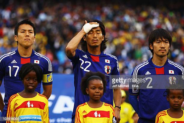 Makoto Hasebe Yuji Nakazawa and Yuki Abe of Japan stand for the national anthem ahead of the 2010 FIFA World Cup South Africa Round of Sixteen match...
