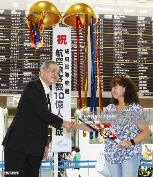 Makoto Natsume president and CEO of Narita International Airport Corp shakes hands with Susanne Sanaei while presenting her with a badmintonlike...