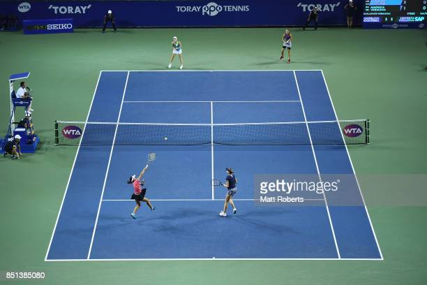 Makoto Ninomiya of Japan plays an overhead volley with partner Renata Voracova of Czech Republic in their doubles semi final match against Daria...