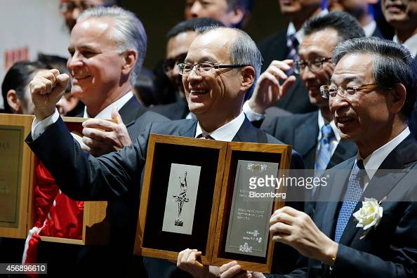Makoto Tani president of Skylark Co center raises his fist while holding a listing notice with Akira Kiyota president of Tokyo Stock Exchange Inc...