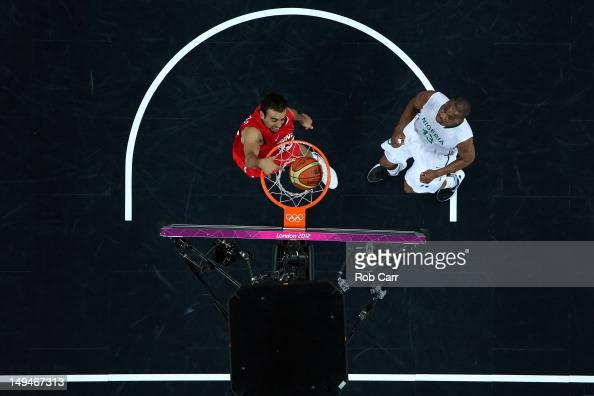 Makram Ben Romdhane of Tunisia dunks the ball over Derrick Obasohan of Nigeria during their Men's Basketball game on Day 2 of the London 2012 Olympic...