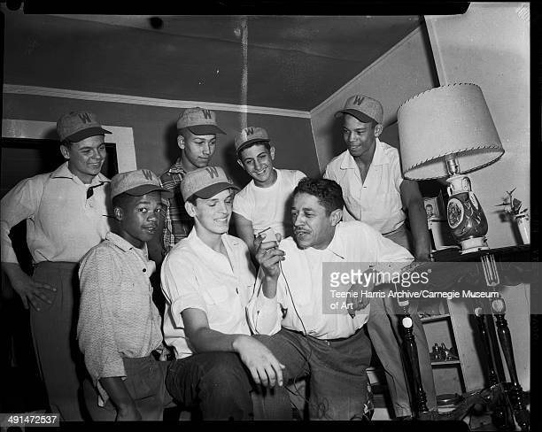 Mal Goode interviewing Lavelle boy and other Little League baseball players wearing hats inscribed 'W' in domestic interior Pittsburgh Pennsylvania...