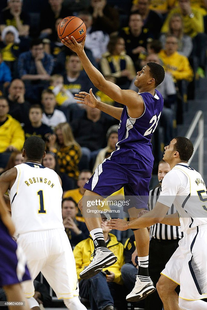 Malachi Alexander #21 of the Holy Cross Crusaders gets a first-half shot off between <a gi-track='captionPersonalityLinkClicked' href=/galleries/search?phrase=Glenn+Robinson+-+Basketball+Player+-+Born+1994&family=editorial&specificpeople=9920511 ng-click='$event.stopPropagation()'>Glenn Robinson</a> III #1 and Jordan Morgan #52 of the Michigan Wolverines at Crisler Center on December 28, 2013 in Ann Arbor, Michigan.