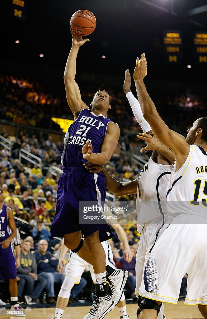 Malachi Alexander #21 of the Holy Cross Crusaders shoots against Jon Horford #15 of the Michigan Wolverines during the second half at Crisler Center on December 28, 2013 in Ann Arbor, Michigan. Michigan won the game 88-66.