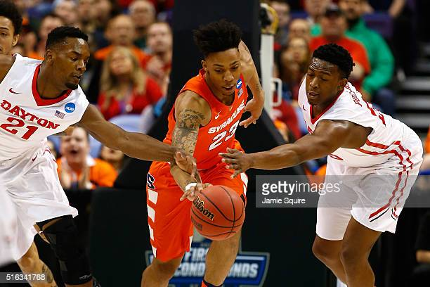 Malachi Richardson of the Syracuse Orange handles the ball in the first half against Dyshawn Pierre and Kendall Pollard of the Dayton Flyers during...
