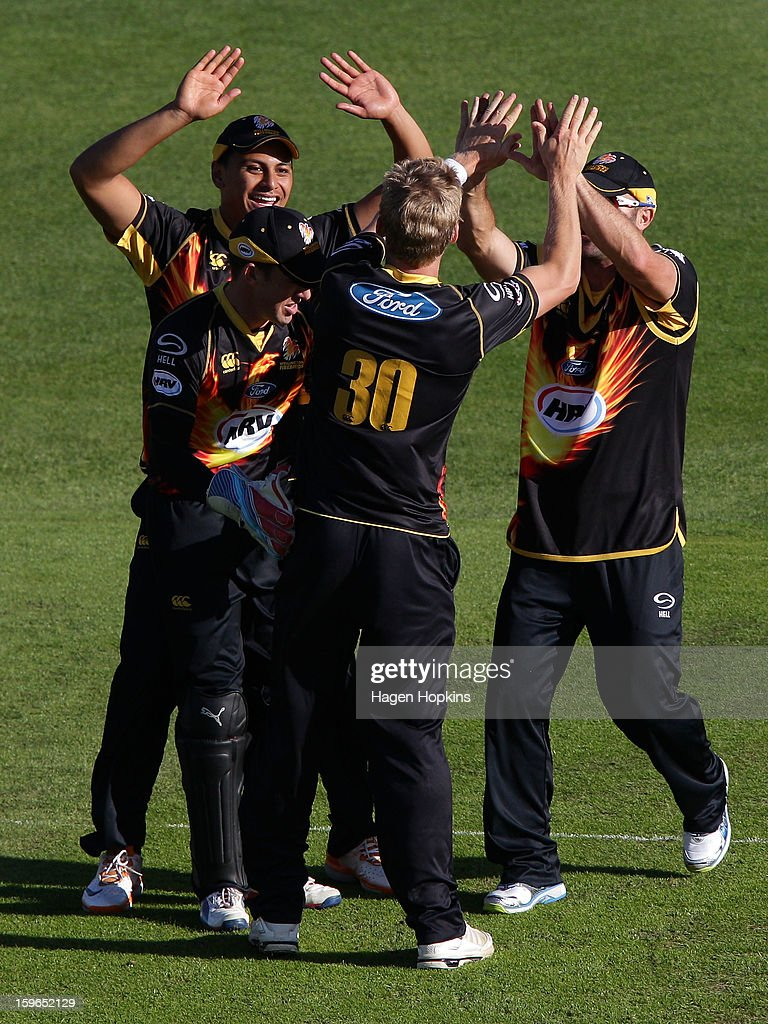 Malaesaili Tugaga (L), Luke Ronchi and Luke Woodcock (R) of Wellington congratulate Scott Kuggeleijn after taking the wicket of Craig Cachopa of Auckland during the HRV Cup Twenty20 Preliminary Final between the Wellington Firebirds and the Auckland Aces at Basin Reserve on January 18, 2013 in Wellington, New Zealand.