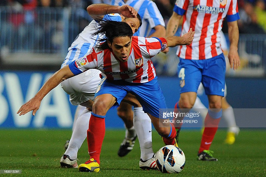 Malaga's Argentinian defender Martin Demichelis (L) vies with Atletico Madrid's Colombian forward Radamel Falcao during the Spanish league football match Malaga CF vs Atletico de Madrid on March 3, 2013 at Rosaleda stadium in Malaga.
