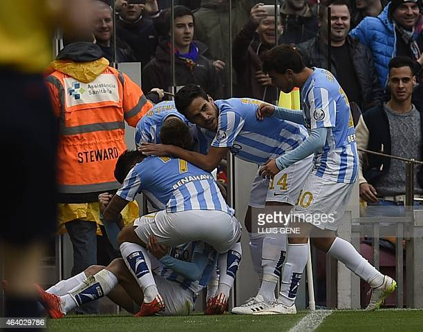 Malaga's Argentinian midfielder Pablo Javier Perez celebrates with team mates after scoring a goal during the Spanish league football match FC...