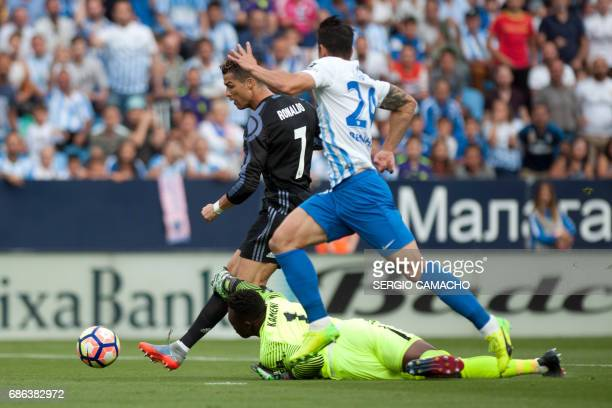 Malaga's Cameroonian goalkeeper Carlos Kameni tries to stop Real Madrid's Portuguese forward Cristiano Ronaldo before scoring a goal during the...
