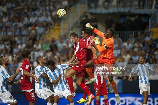 Malaga's Cameroonian goalkeeper Carlos Kameni vies with Sevilla's Polish midfielder Grzegorz Krychowiak and Sevilla's French defender Adil Rami...