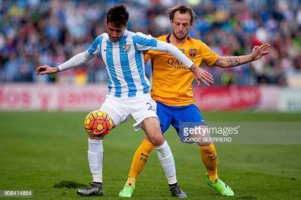 Malaga's Croatian forward Duje Cop vies with Barcelona's Croatian midfielder Ivan Rakitic during the Spanish league football match Malaga CF vs FC...