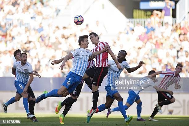 Malaga's defender Diego Javier Llorente vies with Athletic Bilbaos forward Aritz Aduriz during the Spanish league football match Malaga CF vs...
