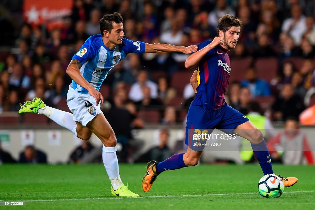 Malaga's defender Luis Hernandez challenges Barcelona's midfielder Sergi Roberto (R) during the Spanish league football match FC Barcelona vs Malaga CF at the Camp Nou stadium in Barcelona on October 21, 2017. / AFP PHOTO / Josep LAGO