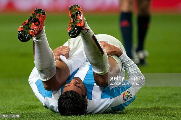 Malaga's defender Miguel Torres falls down during the Spanish league football match Malaga CF vs Club Atletico de Madrid at La Rosaleda stadium in...