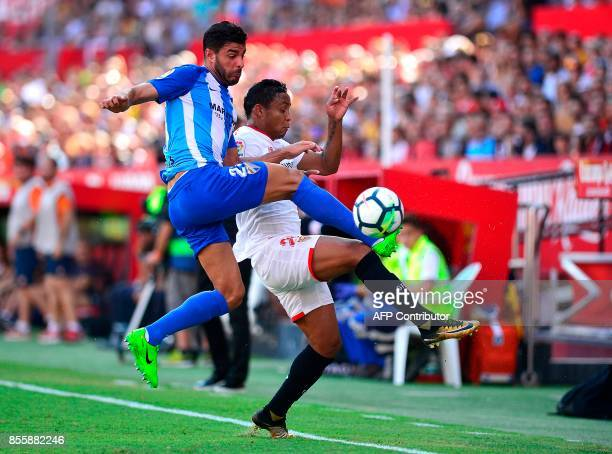 Malaga's defender Miguel Torres vies for the ball with Sevilla's Colombian forward Luis Muriel during the Spanish league football match Sevilla FC vs...